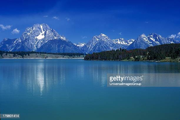 Wyoming Grand Teton National Park Mount Moran viewed over a still Jackson Lake and a clear blue cloudless sky