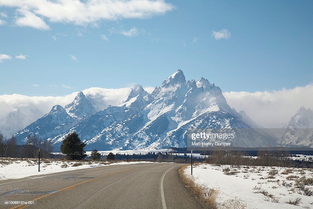 USA, Wyoming, Jackson Hole, Road passing through snow covered landscape, mountains in background : Stockfoto