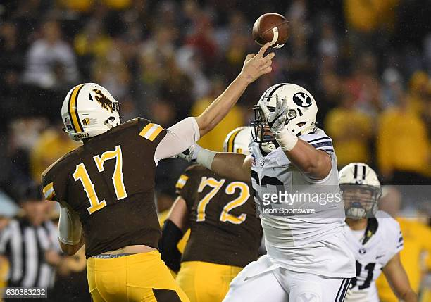 Wyoming Josh Allen throws under pressure from BYU Logan Taele during the San Diego Credit Union Poinsettia Bowl game between the BYU Cougars and the...