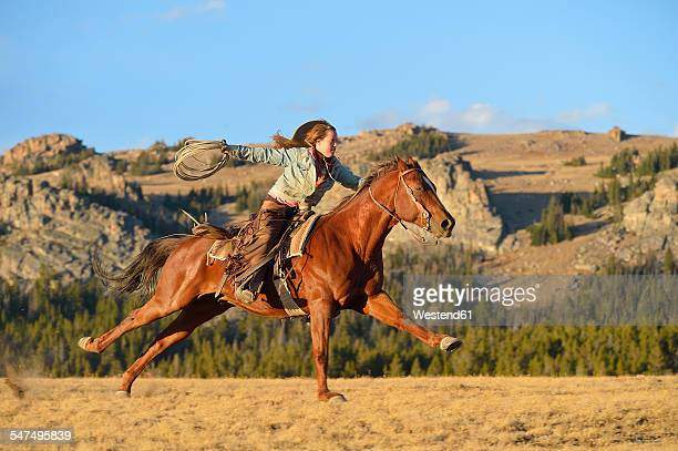 USA, Wyoming, riding cowgirl holding lasso