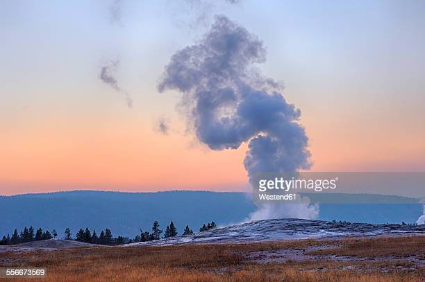 usa, wyoming, yellowstone national park, old faithful geyser erupting at sunset - yellowstone national park stock pictures, royalty-free photos & images