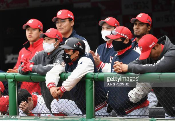 SK Wyverns players wearing face masks watch the game from the dugout during the opening game against Hanwha Eagles for South Korea's new baseball...