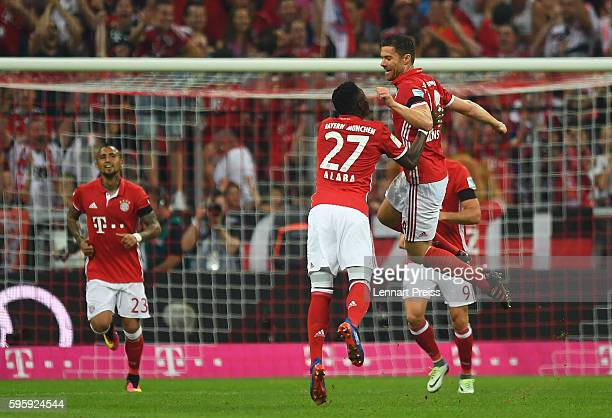 Xabi Alonso and David Alaba of Bayern Muenchen celebrate the opening goal during the Bundesliga match between Bayern Muenchen and Werder Bremen at...