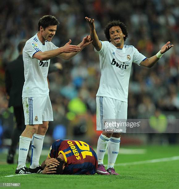 Xabi Alonso and Marcelo of Real Madrid react after Sergio Busquets of Barcelona took a knock during the La Liga match between Real Madrid and...