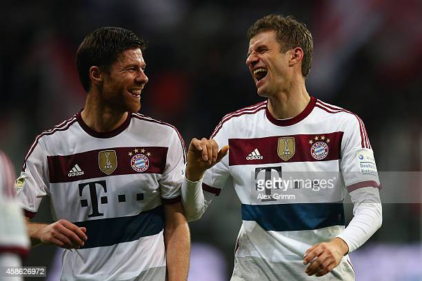 Xabi Alonso and Thomas Mueller of Muenchen laugh after the Bundesliga match between Eintracht Frankfurt and FC Bayern Muenchen at CommerzbankArena on...