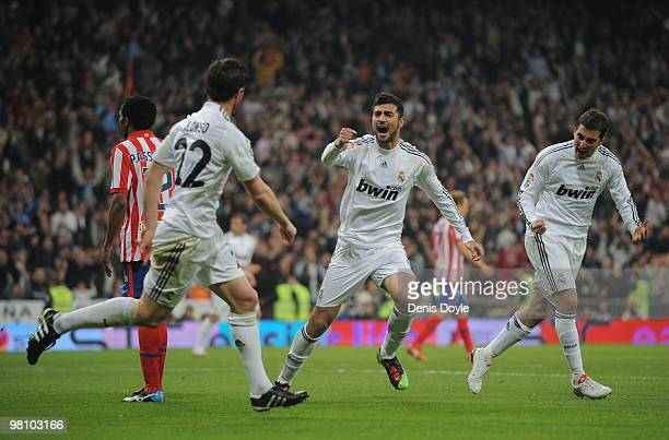 Xabi Alonso celebrates with Raul Albiol and Gonzalo Higuain after scoring Real's first goal during the La Liga match between Real Madrid and Atletico...