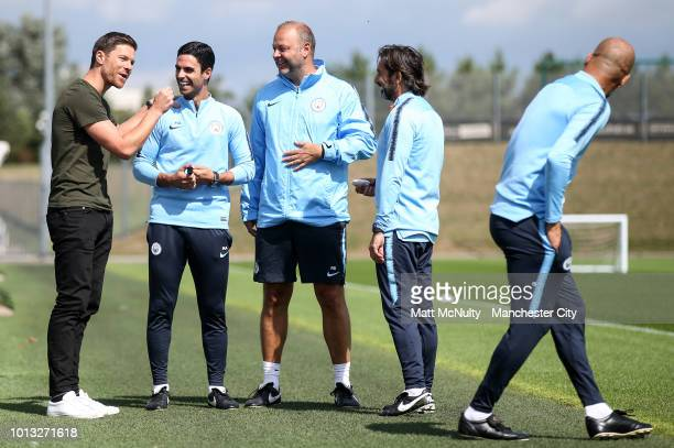 Xabi Alonso greets Manchester City coaches Mikel Arteta Rodolfo Borrell Lorenzo Gonzalez and manager Pep Guardiola during training at Manchester City...