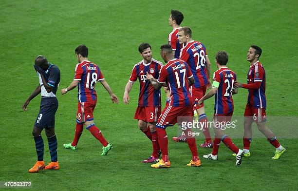 Xabi Alonso of Bayern Muenchen celebrates his goal with teammate Jerome Boateng as Bruno Martins Indi of FC Porto reacts during the Champions League...