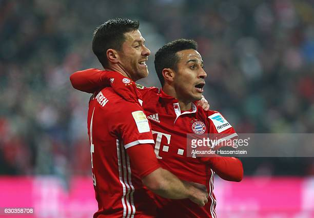 Xabi Alonso of Bayern Muenchen celebrates scoring his sides second goal with Thiago Alcantara of Bayern Muenchen during the Bundesliga match between...