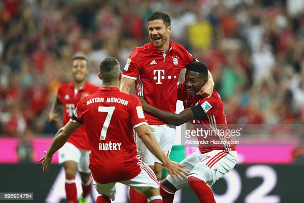 Xabi Alonso of Bayern Muenchen celebrates scoring the first team goal with his team mates Franck Ribery and David Alaba during the Bundesliga match...