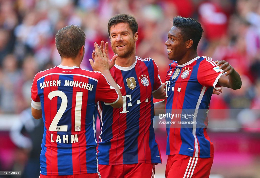Xabi Alonso of Bayern Muenchen celebrates with Philipp Lahm and David Alaba of Bayern Muenchen after scoring their second goal during the Bundesliga match between FC Bayern Muenchen and SV Werder Bremen at Allianz Arena on October 18, 2014 in Munich, Germany.