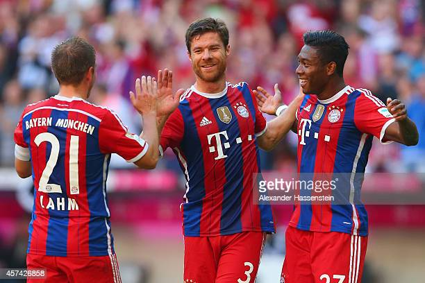 Xabi Alonso of Bayern Muenchen celebrates with Philipp Lahm and David Alaba of Bayern Muenchen after scoring their second goal during the Bundesliga...