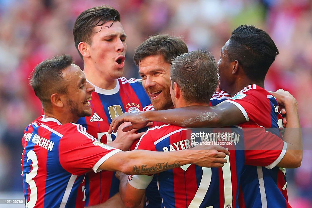 Xabi Alonso of Bayern Muenchen celebrates with team mates after scoring their second goal during the Bundesliga match between FC Bayern Muenchen and SV Werder Bremen at Allianz Arena on October 18, 2014 in Munich, Germany.