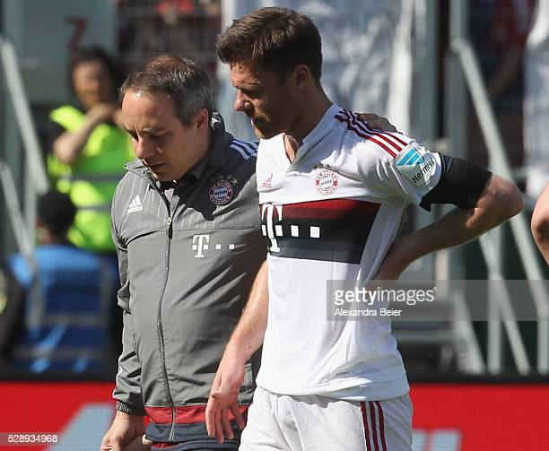 Xabi Alonso of Bayern Muenchen is assisted by team doctor Volker Braun during the Bundesliga match between FC Bayern Muenchen and FC Ingolstadt at...