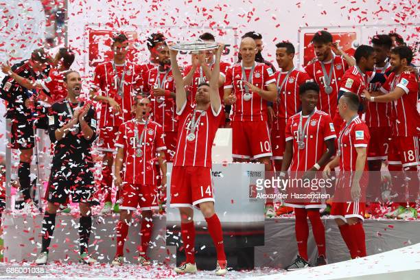 Xabi Alonso of Bayern Muenchen lifts the Championship trophy in celebration of the 67th German Championship title following the Bundesliga match...