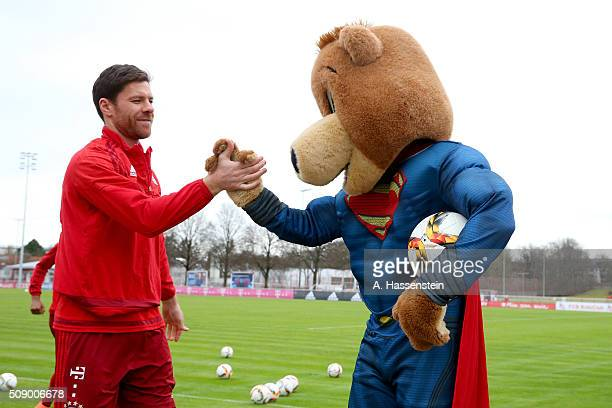 Xabi Alonso of Bayern Muenchen reacts with mascot Bernie dressed as Superman prior to a training session at Bayern Muenchen's training ground...