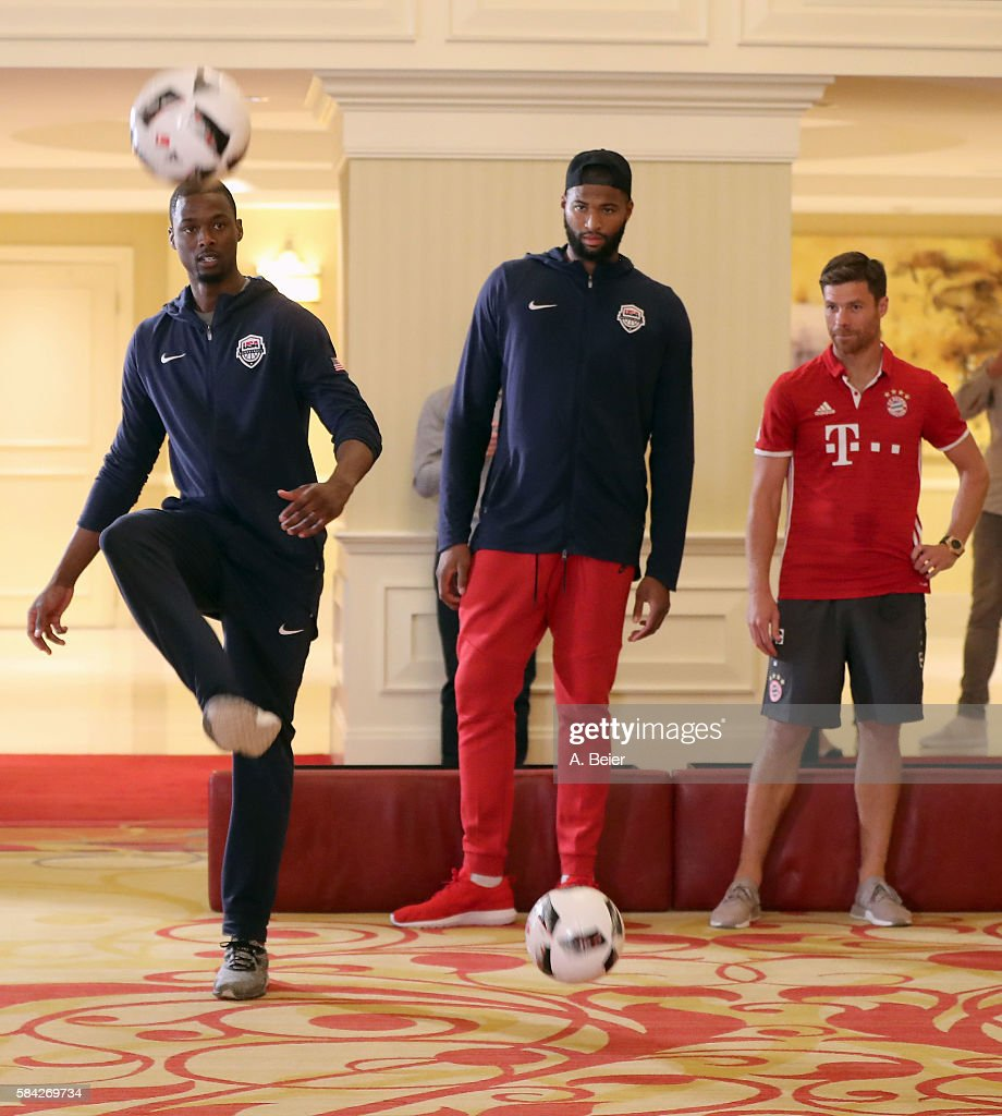 Xabi Alonso (R) of Bayern Muenchen watches NBA players DeMarcus Cousins (C) of Sacramento Kings and Harrison Barnes of Dallas Mavericks playing soccer in an activity session during the AUDI Summer Tour USA 2016 on July 28, 2016 in Chicago, Illinois.