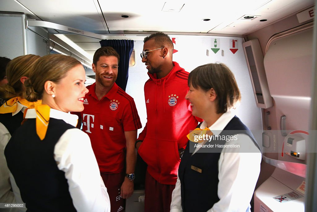 Xabi Alonso (L) of FC Bayern Muenchen and his team mate Jerome Boateng talk to air hostesses whilst her team charter flight to Shanghai is grounded at Apron on Beijing Capital Airport during day 3 of the FC Bayern Audi China Summer Pre-Season Tour on July 19, 2015 in Beijing, China.