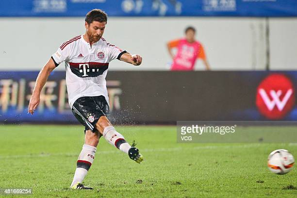 Xabi Alonso of FC Bayern Muenchen scores the second penalty kick at the penalty shootout during the international friendly match between Guangzhou...