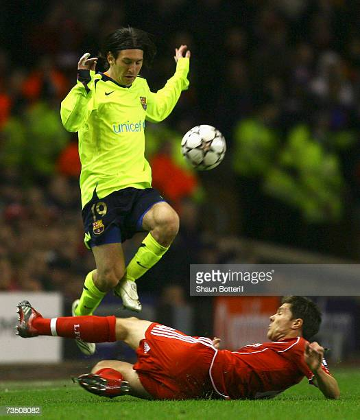 Xabi Alonso of Liverpool slides in to challenge Lionel Messi of Barcelonaduring the UEFA Champions League round of sixteen second leg match between...