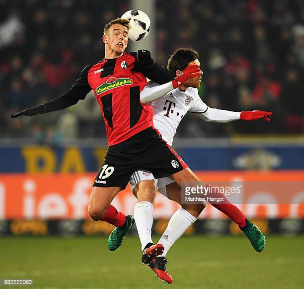 Xabi Alonso of Muechen challenges Janik Haberer of Freiburg during the Bundesliga match between SC Freiburg and Bayern Muenchen at SchwarzwaldStadion...
