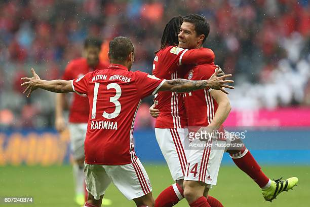 Xabi Alonso of Muenchen celebrates scoring the 2nd team goal with his team mate Renato Sanches and Rafinha during the Bundesliga match between Bayern...