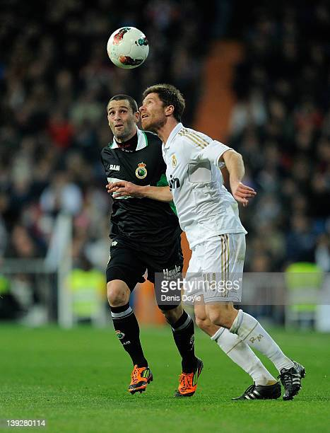 Xabi Alonso of Real Madrid battles for the ball against Adrian of Real Racing Club during the La Liga match between Real Madrid and Real Racing Club...