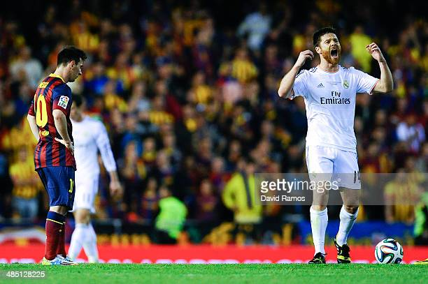 Xabi Alonso of Real Madrid CF celebrates past Lionel Messi of FC Barcelona after his teammate Gareth Bale of Real Madrid CF scored the winning goal...