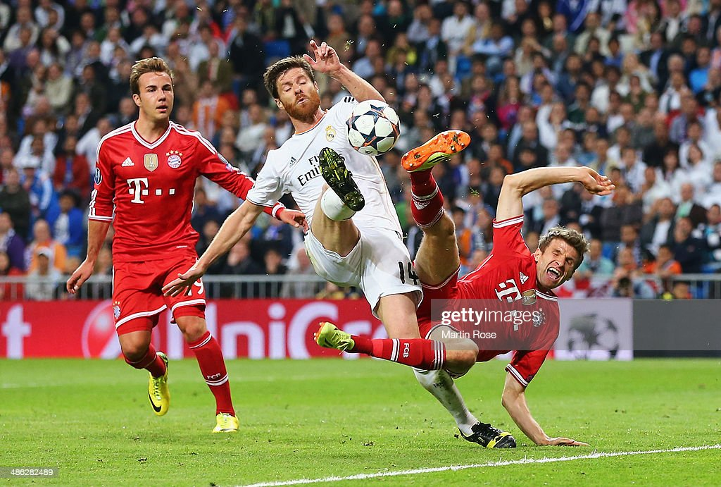 Xabi Alonso of Real Madrid challenges Thomas Mueller of Bayern Muenchen watched by Mario Goetze of Bayern Muenchen during the UEFA Champions League semi-final first leg match between Real Madrid and FC Bayern Muenchen at the Estadio Santiago Bernabeu on April 23, 2014 in Madrid, Spain.