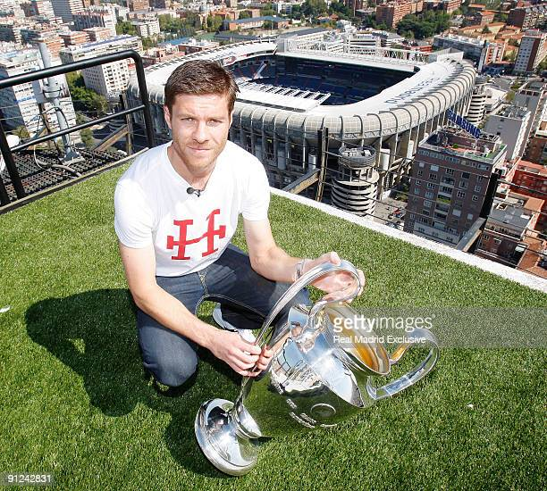 Xabi Alonso of Real Madrid poses with a European Cup and the Santiago Bernabeu Stadium during a interview at Torre Europa on September 29 2009 in...