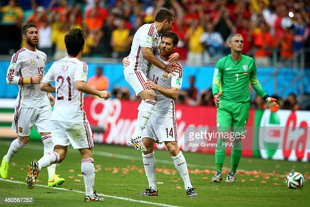 Xabi Alonso of Spain celebrates with teammates after scoring a goal from the penalty spot during the 2014 FIFA World Cup Brazil Group B match between...