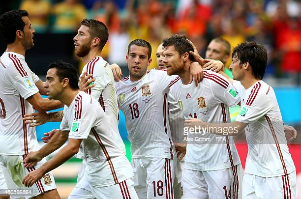 Xabi Alonso of Spain celebrates with teammates after scoring from the penalty spot during the 2014 FIFA World Cup Brazil Group B match between Spain...