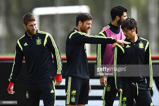 Xabi Alonso of Spain chats with his teammates Sergio Ramos and David Silva of Spain during a Spain training session at Centro de Entrenamiento do...