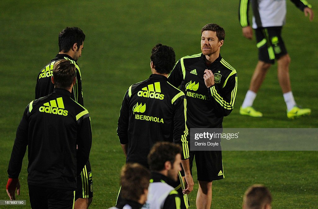 Xabi Alonso of Spain chats with team-mates during a training session ahead of their international friendly against Equatorial Guinea on November 13, 2013 in Las Rozas, Spain.