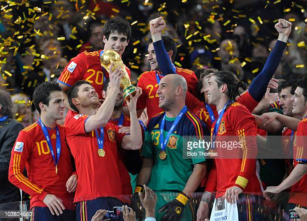 Xabi Alonso of Spain lifts the trophy and celebrates with teammates after the 2010 FIFA World Cup Final between the Netherlands and Spain on July 11...