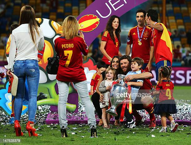 Xabi Alonso of Spain poses with his wife Nagore Aramburu their son Jontxu Alonso and the trophy following victory in the UEFA EURO 2012 final match...