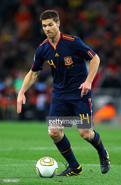 Xabi Alonso of Spain runs with the ball during the 2010 FIFA World Cup South Africa Final match between Netherlands and Spain at Soccer City Stadium...