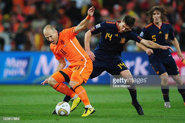 Xabi Alonso of Spain tackles Arjen Robben of the Netherlands during the 2010 FIFA World Cup South Africa Final match between Netherlands and Spain at...