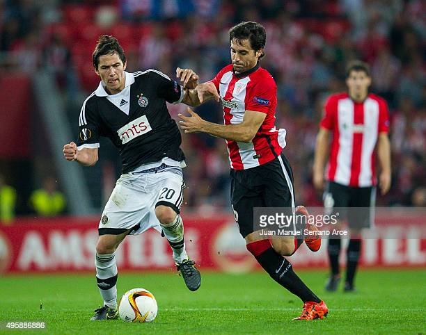 Xabier Etxeita of Athletic Club duels for the ball with Sasa Lukic of FK Partizan during the UEFA Europa League match between Athletic Club and FK...