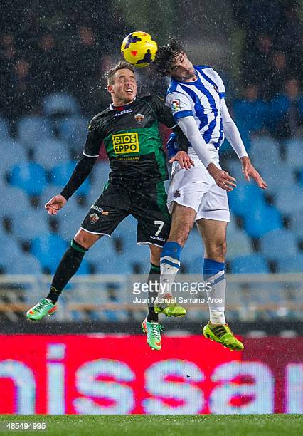 Xabier Prieto of Real Sociedad duels for the ball with Aaron Niguez of Elche FC during the La Liga match between Real Sociedad de Futbol and Elche FC...