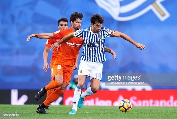 Xabier Prieto of Real Sociedad duels for the ball with Adrian Gonzalez of Malaga CF during the La Liga match between Real Sociedad de Futbol and Real...