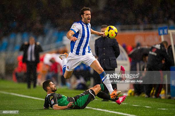 Xabier Prieto of Real Sociedad duels for the ball with Alberto Botian of Elche FC during the La Liga match between Real Sociedad de Futbol and Elche...