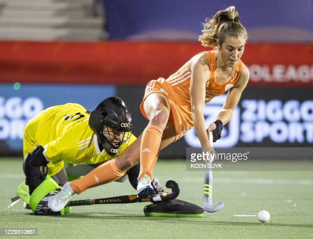 Xan de Waard of the Netherlands vies for the ball with goalkeeper Sabbie Heesh of Great Britain during their women's field hockey international match...