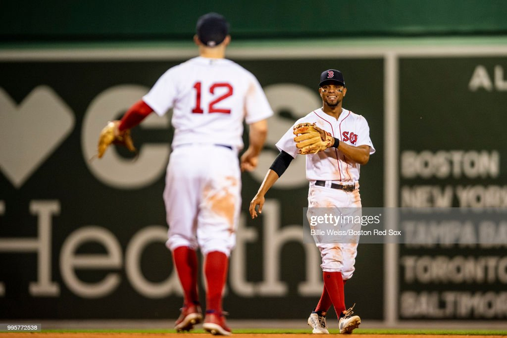 Xander Bogaerts #2 and Brock Holt #12 of the Boston Red Sox react after recording the final out of a game against the Texas Rangers on July 10, 2018 at Fenway Park in Boston, Massachusetts.
