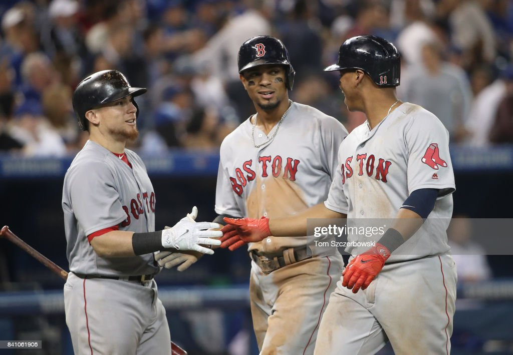 Xander Bogaerts #2 and Rafael Devers #11 of the Boston Red Sox are congratulated by Christian Vazquez #7 after both scored on a two-run single by Mitch Moreland in the eighth inning during MLB game action against the Toronto Blue Jays at Rogers Centre on August 30, 2017 in Toronto, Canada.