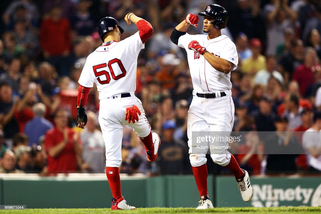 Xander Bogaerts #2 bumps forearms with Mookie Betts #50 of the Boston Red Sox after hitting a three-run home run in the fifth inning of a game against the Baltimore Orioles at Fenway Park on May 17, 2018 in Boston, Massachusetts.