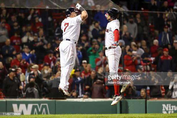 Xander Bogaerts high fives Christian Vazquez of the Boston Red Sox after hitting a solo home run in the seventh inning of a game against the Texas...