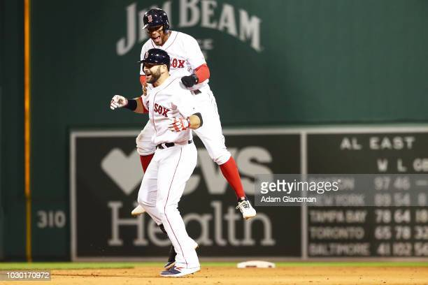 Xander Bogaerts jumps on the back of Mitch Moreland of the Boston Red Sox after he hit the gamewinning walkoff hit in the ninth inning of a game...