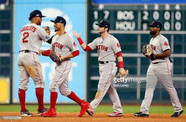 Xander Bogaerts, Mookie Betts, Andrew Benintendi, and Jackie Bradley Jr. #19 of the Boston Red Sox celebrate defeating the Houston Astros 8-2 in Game...