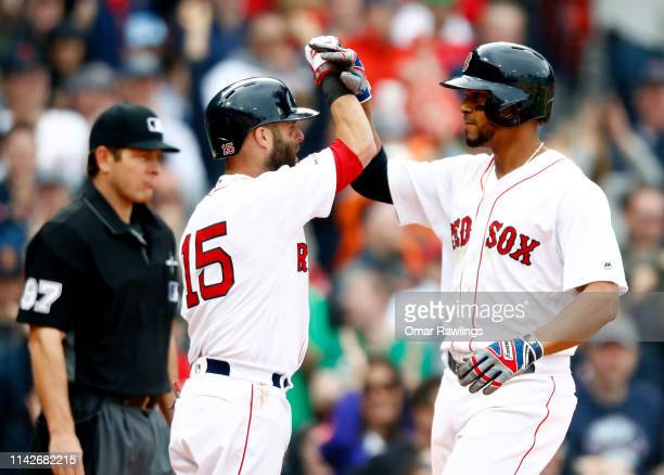 Xander Bogaerts of the Boston Red Sox and Dustin Pedroia of the Boston Red Sox celebrate after crossing home plate in the bottom of the eighth inning...